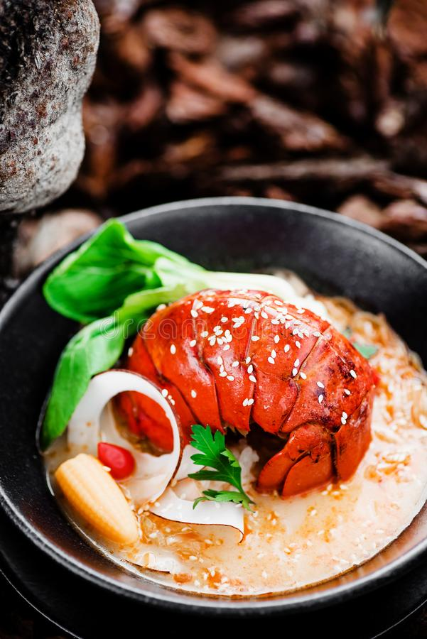 Spicy Soup with lobster tail, pak choi cabbage, vegetables and sesame in a black plate. Close-up. Beautiful serving of gourmet seafood dishes stock photos
