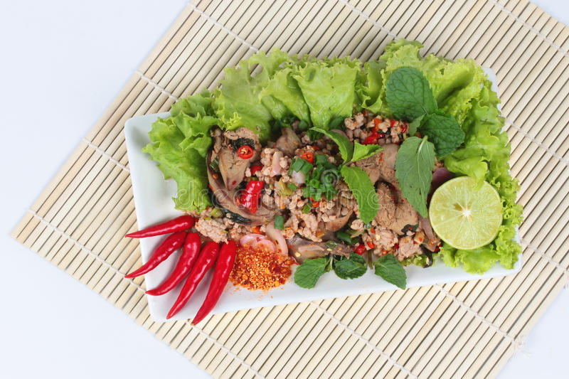 Spicy and sour mixed herb salad with pork and chicken on bamboo and white.Top view. Spicy and sour mixed herb salad with pork and chicken is Thai cuisine as stock photo
