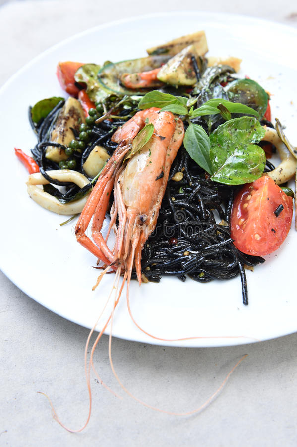 Spicy squid ink spaghetti with green mussel and shrimp.  royalty free stock photography