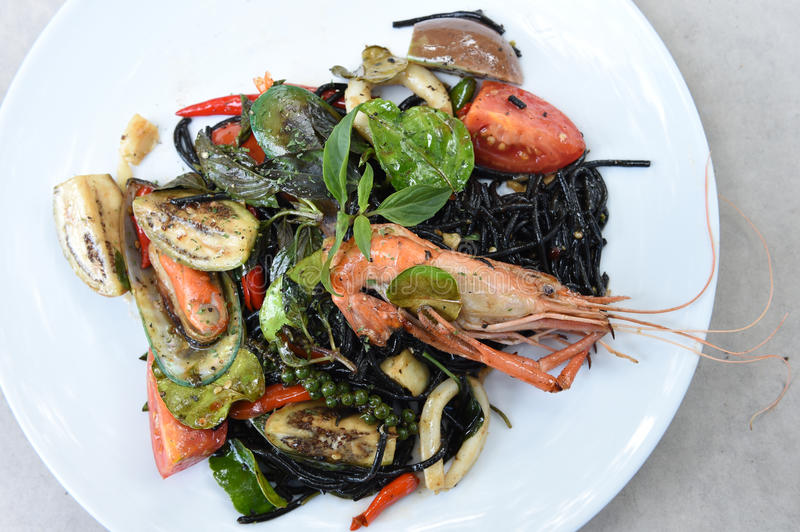 Spicy squid ink spaghetti with green mussel and shrimp.  royalty free stock images