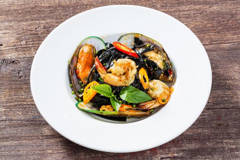 Spicy squid ink spaghetti with green mussel and shrimp. Close up spicy squid ink spaghetti with green mussel and shrimp royalty free stock photography