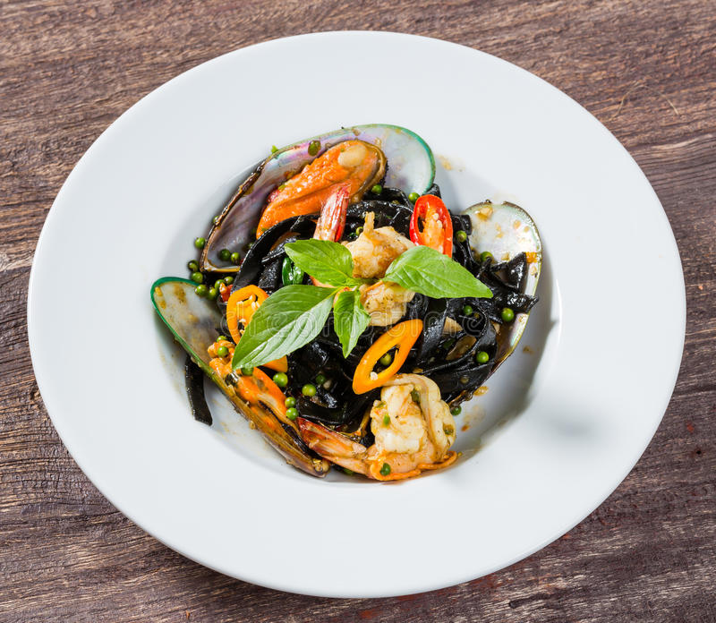 Spicy squid ink spaghetti with green mussel and shrimp. Close up spicy squid ink spaghetti with green mussel and shrimp stock image