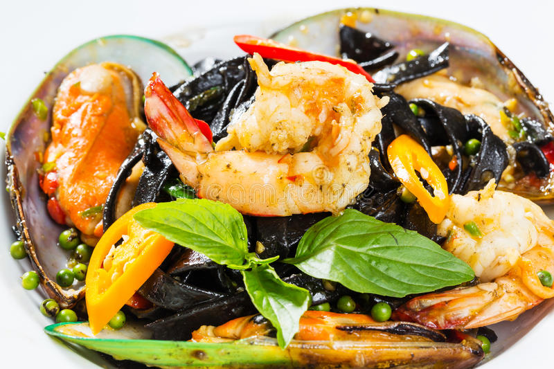 Spicy squid ink spaghetti with green mussel and shrimp. Close up spicy squid ink spaghetti with green mussel and shrimp stock photo