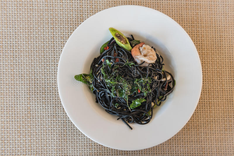 Spicy squid ink spaghetti with green mussel and shrimp. Top view stock image