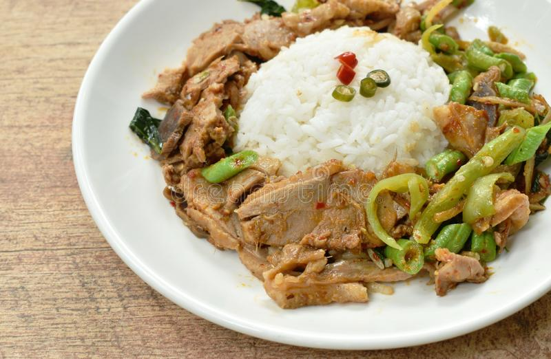 Spicy stir fried duck meat curry on rice in plate stock images