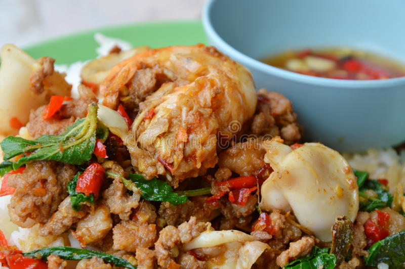 Spicy stir-fried mixed seafood and chop pork with basil leaf on rice stock images