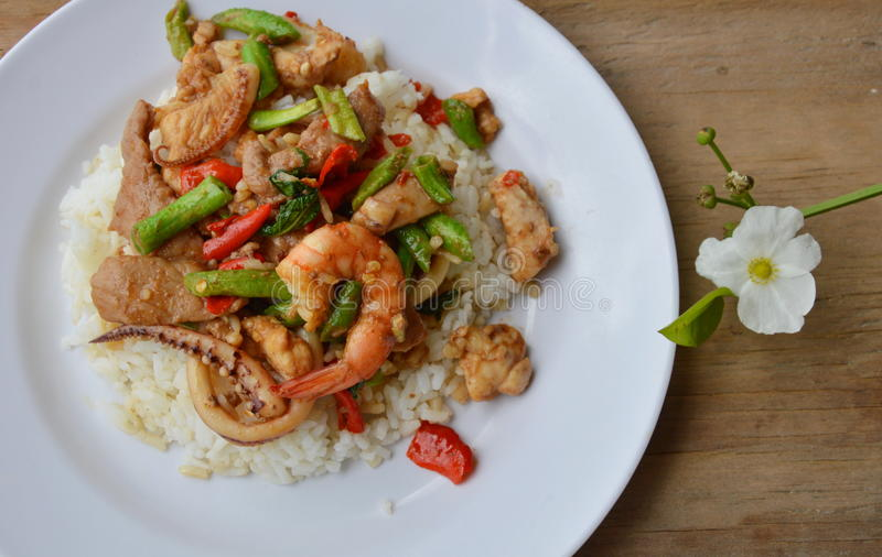 Spicy stir fried mixed seafood and pork with basil leaf on rice stock photography