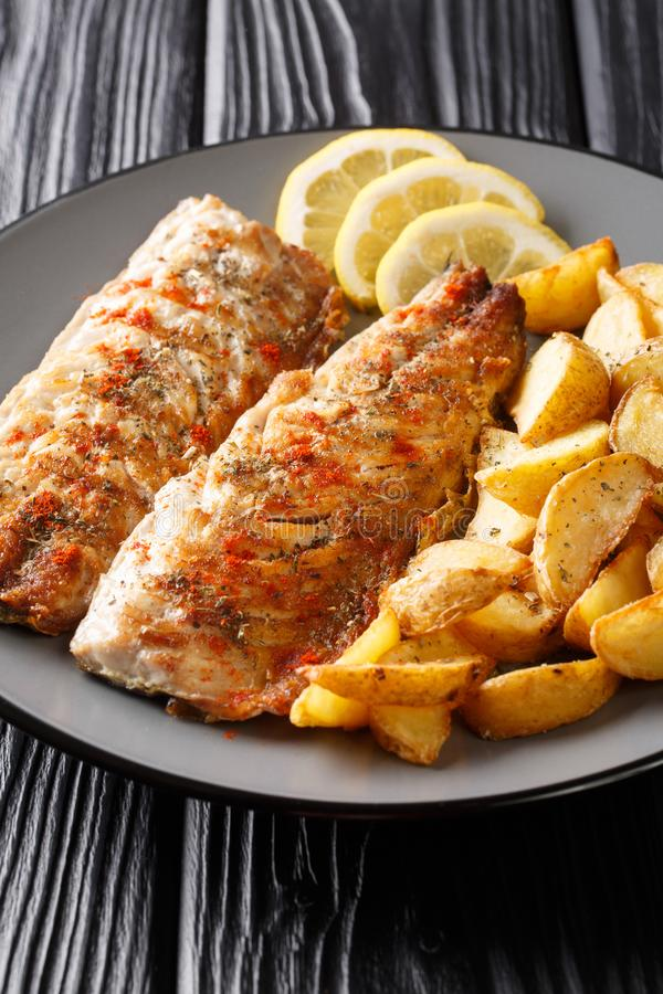 Spicy tasty grilled mackerel filet with potato wedges and lemon close-up on a plate. vertical royalty free stock photos