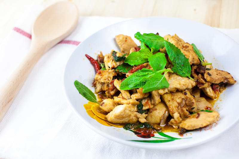 Spicy Thai basil chicken ready to eat on traditional plate. (Shallow aperture intended for the aesthetic quality of the blur stock photos