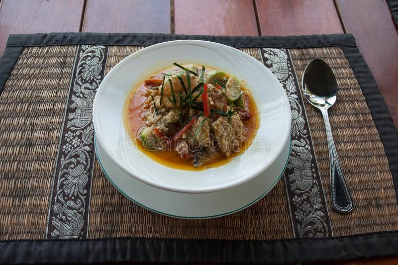 Spicy Thai soup with fish, seafood and vegetables. On the table stock image