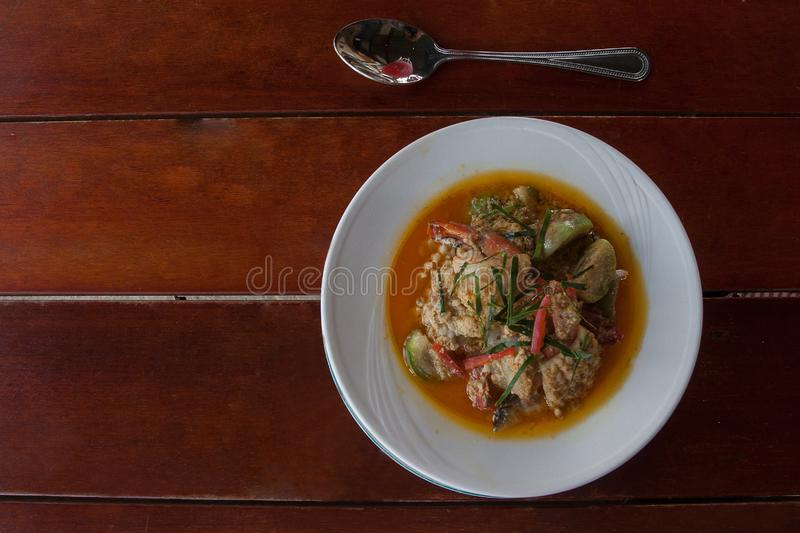 Spicy Thai soup with fish, seafood and vegetables. On the table royalty free stock photos