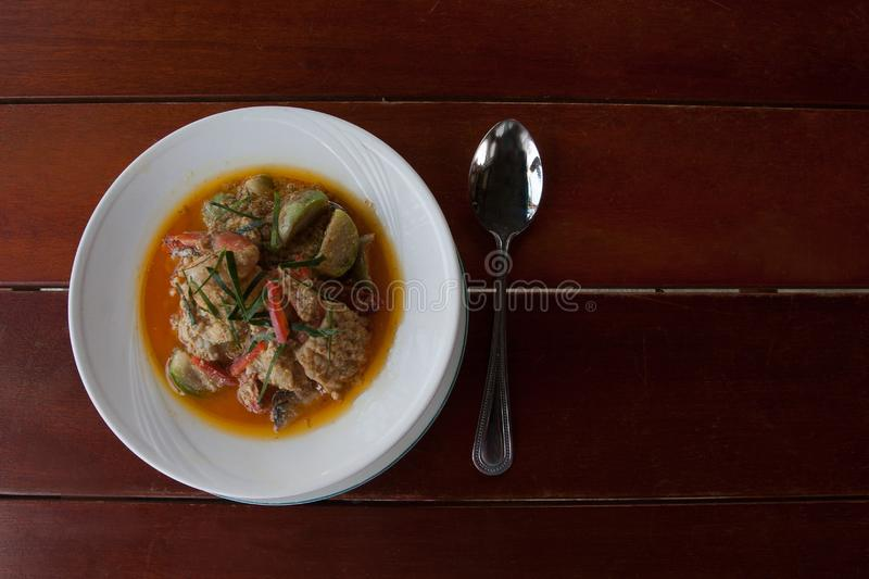 Spicy Thai soup with fish, seafood and vegetables. On the table stock images