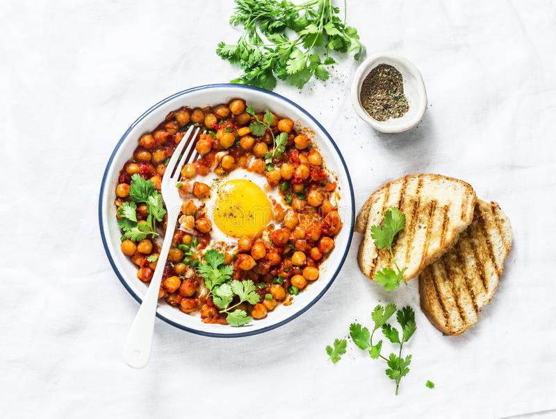Spicy tomato sauce chickpeas baked eggs on a light background, top view. Delicious healthy breakfast royalty free stock photo