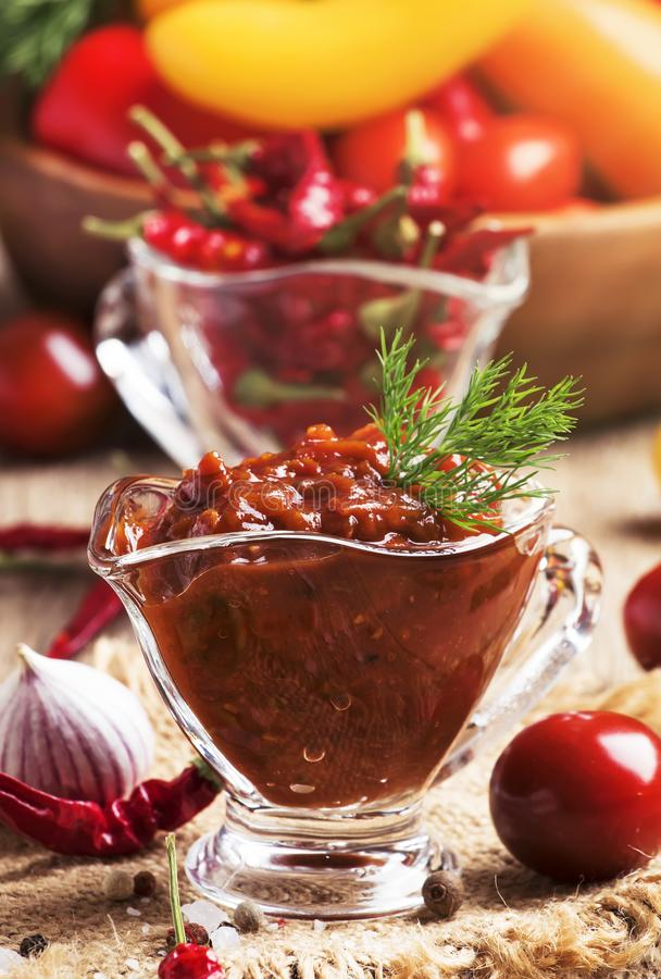 Spicy tomato sauce with pepper and garlic in a glass bowl on the vintage wooden table, selective focus stock photos