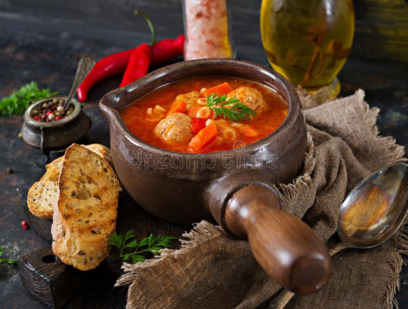 Spicy tomato soup with meatballs, pasta and vegetables. Healthy dinner. Black background royalty free stock photos