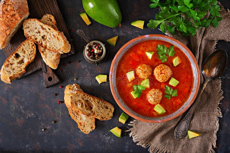 Spicy tomato soup with meatballs and vegetables. Served with avocado and parsley. Healthy dinner.Flat lay. stock photography