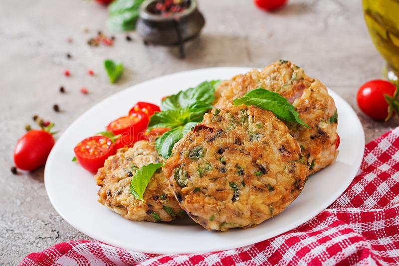 Spicy vegan burgers with rice, chickpeas and herbs. Salad tomato and basil. royalty free stock image