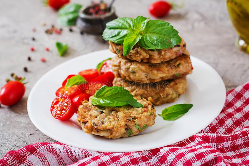 Spicy vegan burgers with rice, chickpeas and herbs. Salad tomato and basil. stock photos