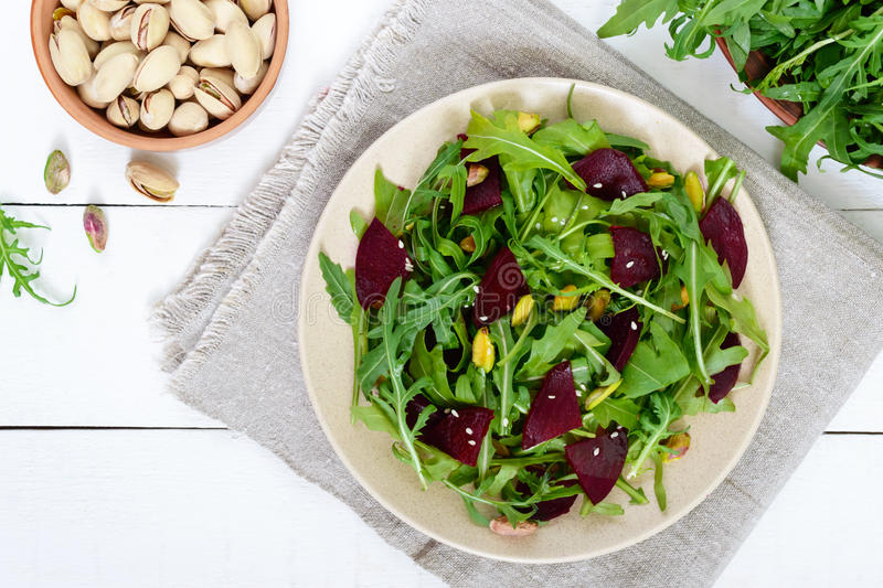 Spicy vegan salad of beets, arugula, pistachio nuts on a plate on a white background. Top view royalty free stock photos