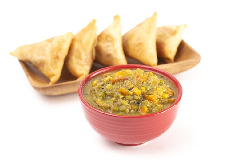 Spicy Vegetable Curry Isolated on a White Background with Samosas in the Background royalty free stock photo