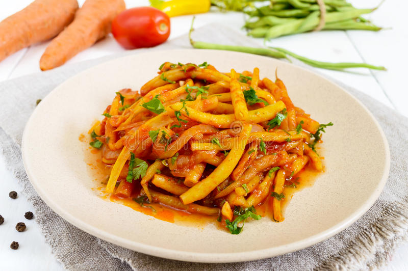 Spicy warm salad of green beans in tomato sauce on a plate on a white wooden background stock photos