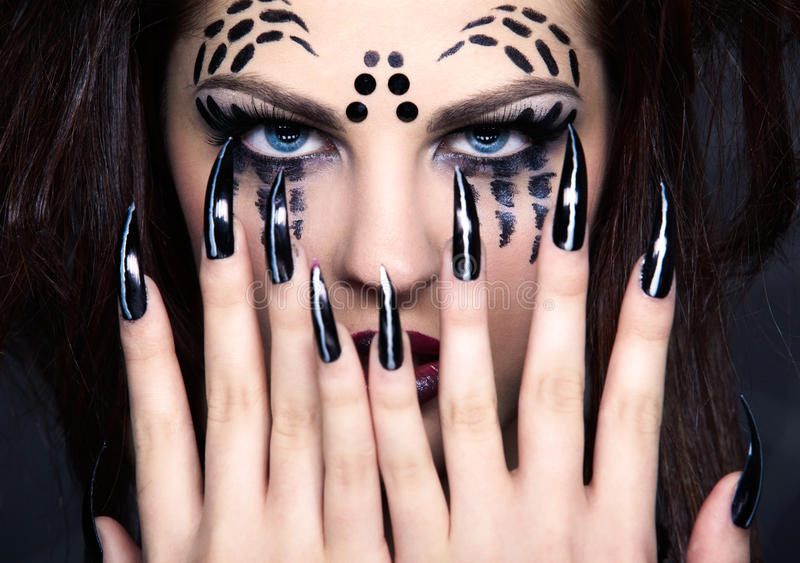 Spider girl. Close up portrait of girl with spider bodyart of face zone and black finger-nails stock photo