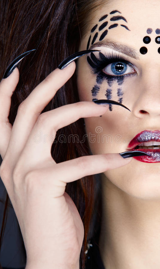 Spider girl. Close up portrait of girl with spider bodyart of face zone and black finger-nails royalty free stock images