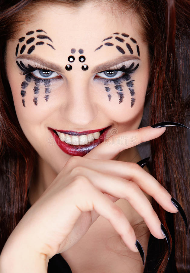 Spider girl. Close up portrait of girl with spider bodyart of face zone and black finger-nails stock image