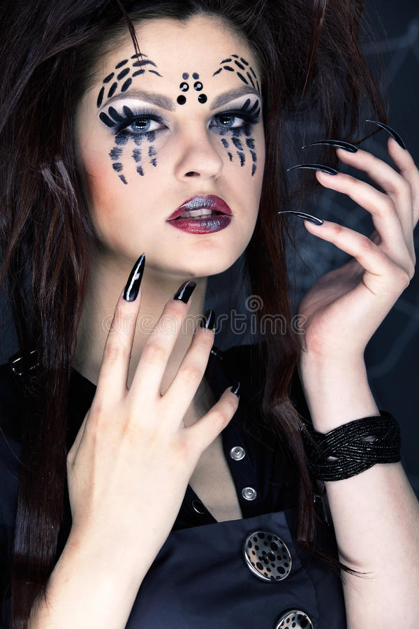 Spider girl. Close up portrait of girl with spider bodyart of face zone and black finger-nails stock photos