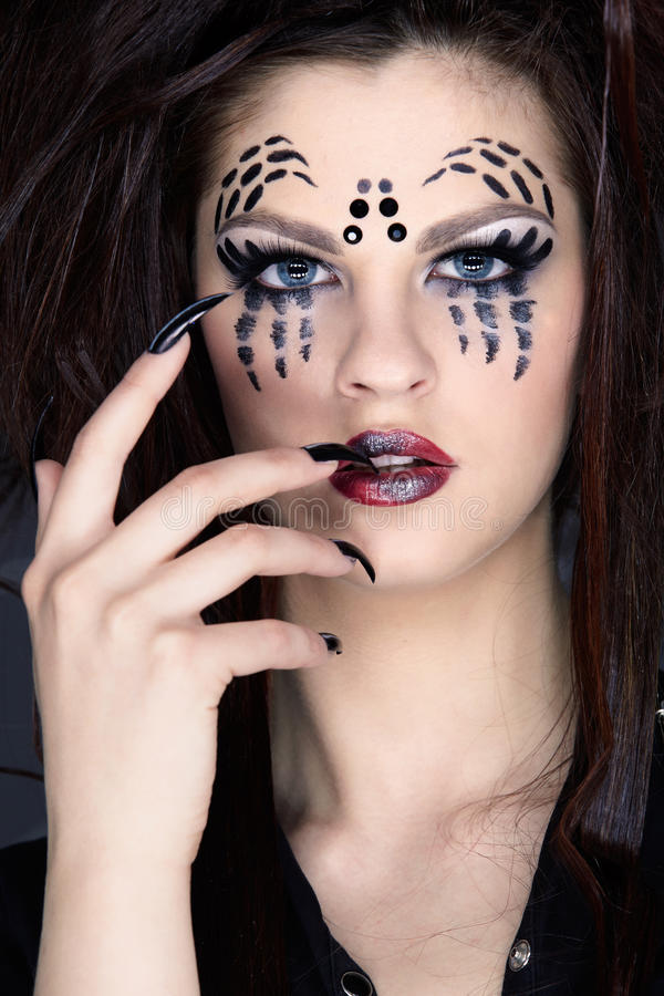Spider girl. Close up portrait of girl with spider bodyart of face zone and black finger-nails royalty free stock photo