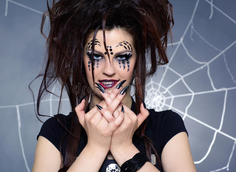 Spider girl. Close up portrait of girl with spider bodyart of face zone and black finger-nails royalty free stock image