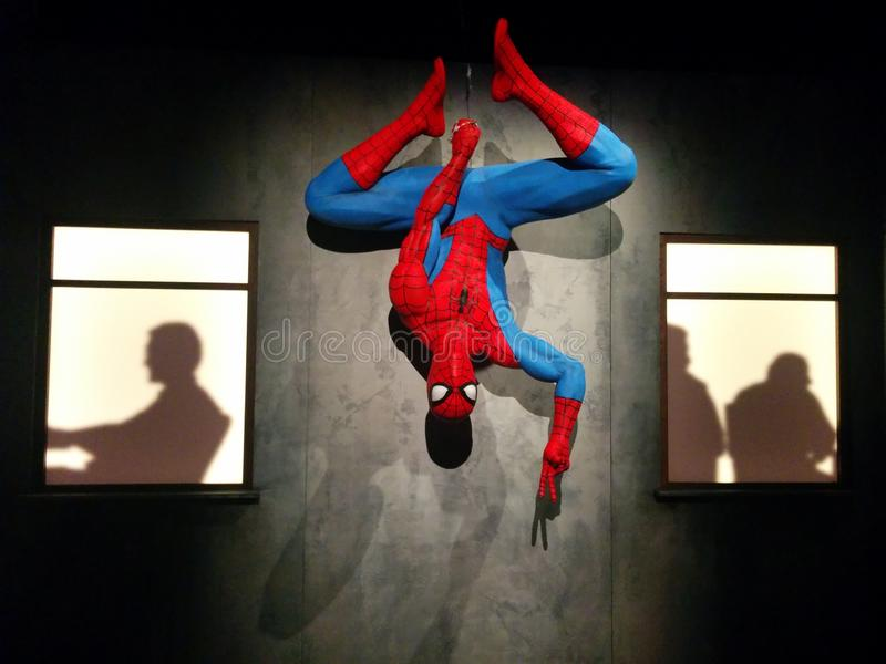 Spider-Man hanging upside down at MoPOP exhibit in Seattle. Spider-Man hanging upside down and giving the peace sign between two windows with silhouettes in the stock images
