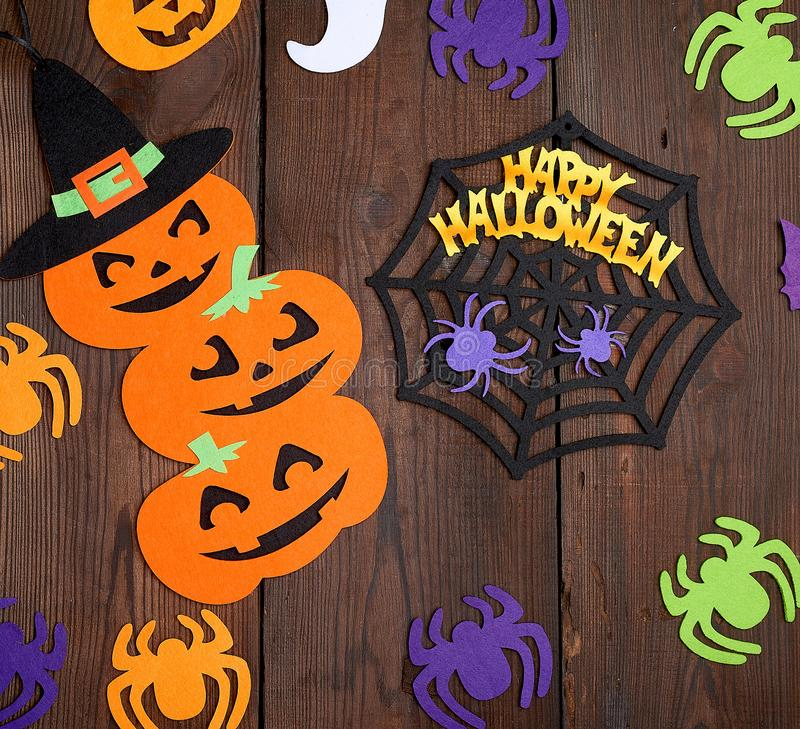 Spider and orange pumpkin felt figures on a brown background. Halloween festive backdrop royalty free stock image