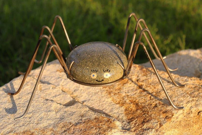 Spider rock with metal legs garden art royalty free stock image