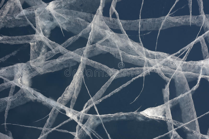 Spider web of tension cracks in thick layer of ice royalty free stock images