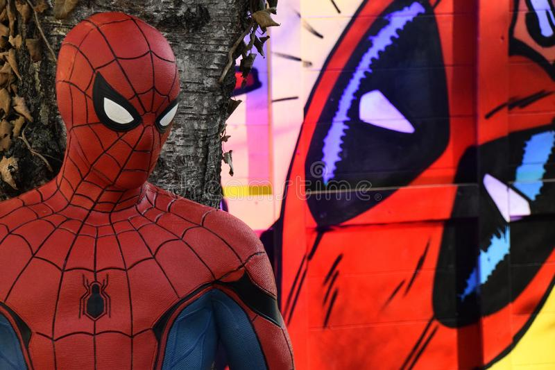 Spiderman and Venom. ZAGREB - DECEMBER 2018: Advent in Zagreb kids fun zone on Strossmayer square, Spiderman figure hidden behind the tree wached from behind by stock image