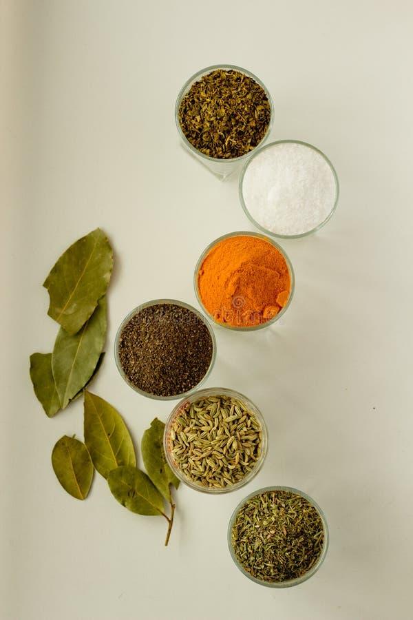Spieces e hierbas en pequeños vidrios imagenes de archivo