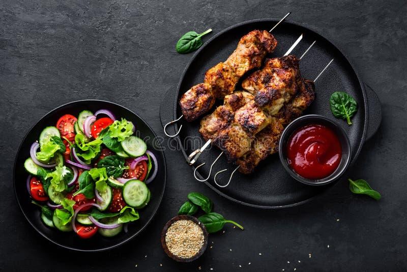 Spiedi arrostiti della carne, kebab ed insalata di verdure sana del pomodoro, del cetriolo, della cipolla, degli spinaci, della l immagini stock