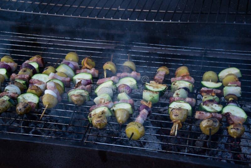 Spiedi con le fette di patate, zucchini, bacon, funghi, cipolla, cavolo rapa grigliato sopra i carboni sulla griglia del barbecue fotografia stock libera da diritti
