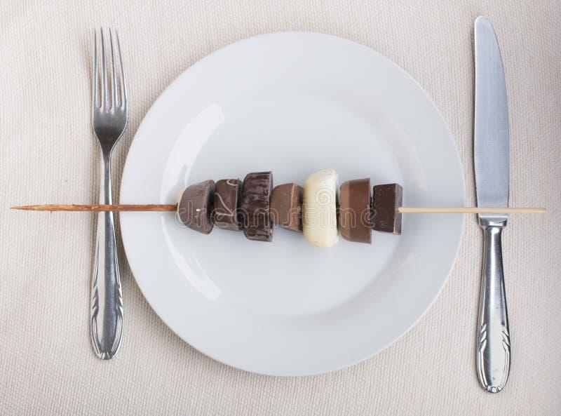 Spiedi del cioccolato sul piatto bianco fotografie stock libere da diritti