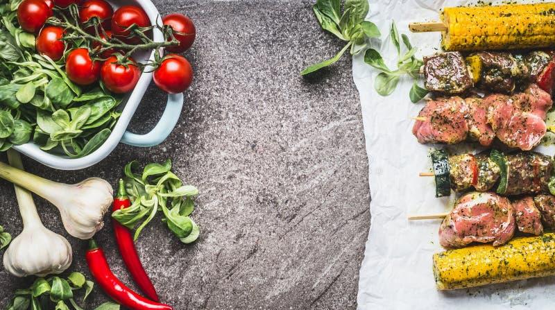 Spiedi delle verdure e della carne che cucinano preparazione per la griglia o che arrostiscono sul fondo concreto grigio immagine stock