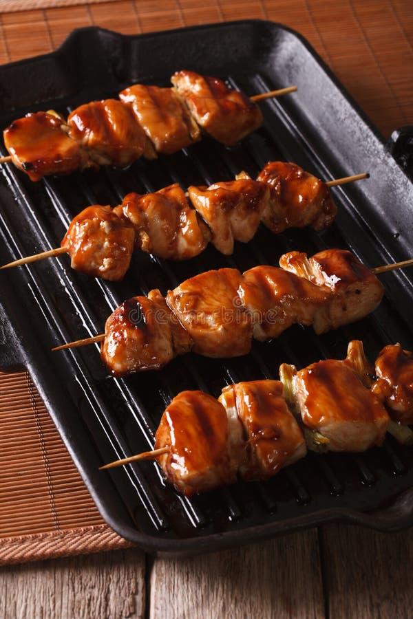 Spiedi giapponesi di yakitori del pollo su una griglia fine di verticale fotografia stock libera da diritti
