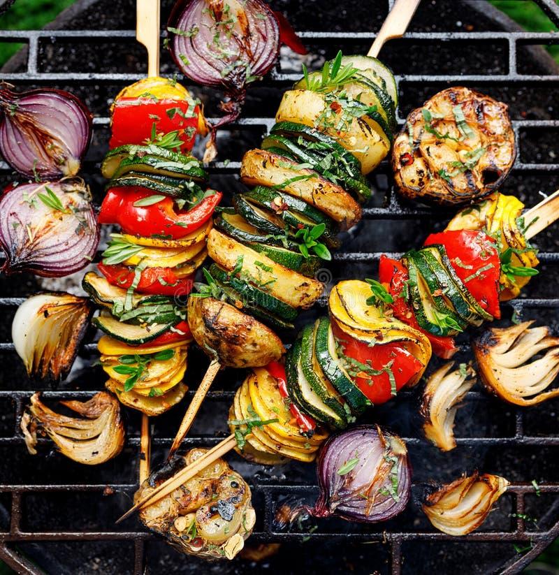 Spiedi vegetariani, spiedi di verdure arrostiti dello zucchini, peperoni e patate con l'aggiunta delle erbe e dell'olio d'oliva a fotografia stock
