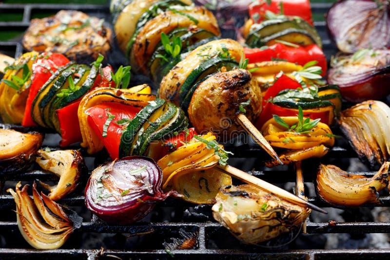 Spiedi vegetariani, spiedi di verdure arrostiti dello zucchini, peperoni e patate con l'aggiunta delle erbe e dell'olio d'oliva a immagini stock