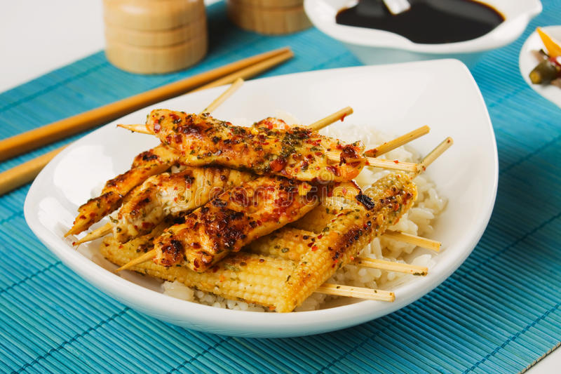 Spiedo asiatico del pollo con il mais ed il riso di bambino immagine stock