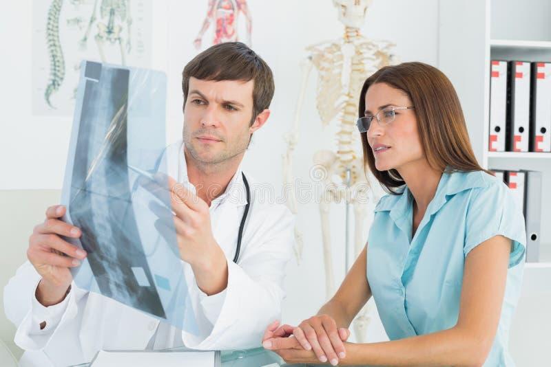 Spiegazione maschio di medico spinexray al paziente femminile immagini stock