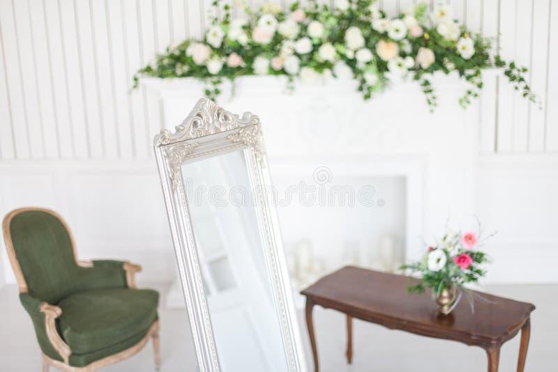 Spiegel in klassiek helder binnenland met open haard en leunstoel De lentebinnenhuisarchitectuur met bloemen stock foto's