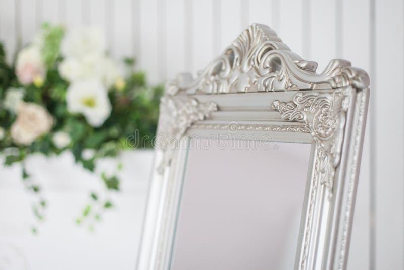 Spiegel in klassiek helder binnenland met open haard en leunstoel De lentebinnenhuisarchitectuur met bloemen royalty-vrije stock foto's