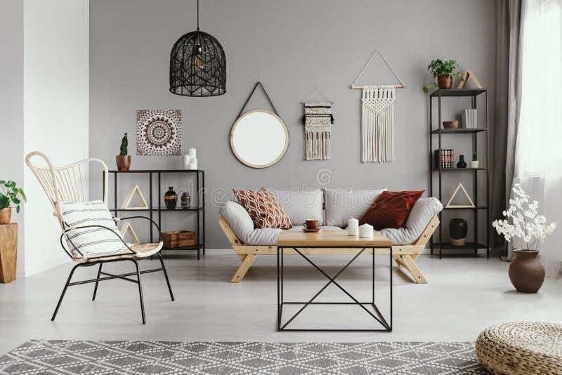 Spiegel, macramé en grafisch op de grijze muur van warme ethnowoonkamer royalty-vrije stock afbeeldingen