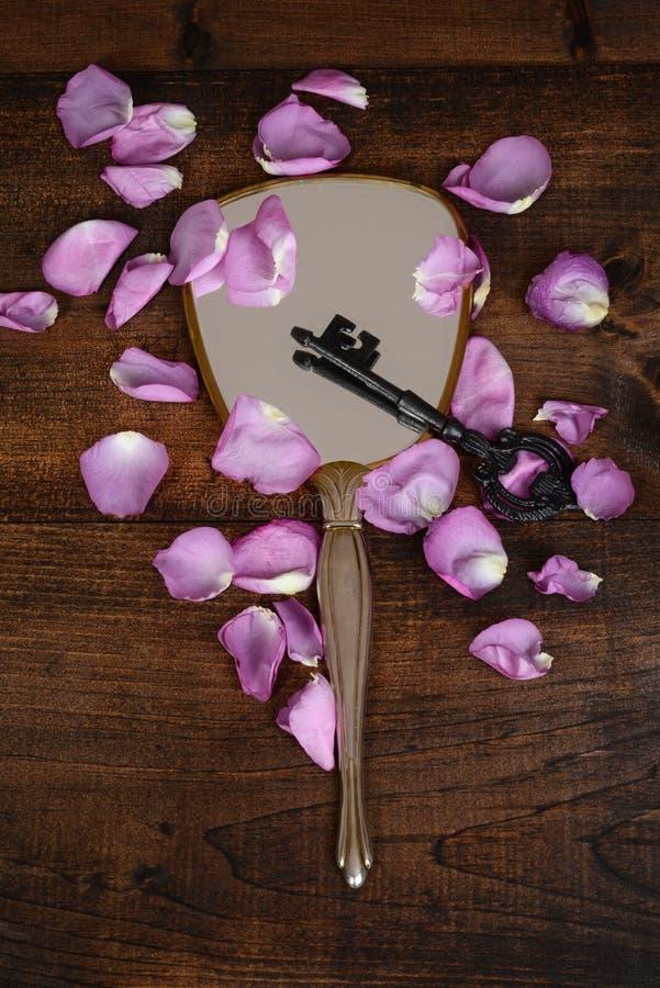 Spiegel mit den Schlüssel- und rosafarbenen Blumenblättern lizenzfreies stockbild